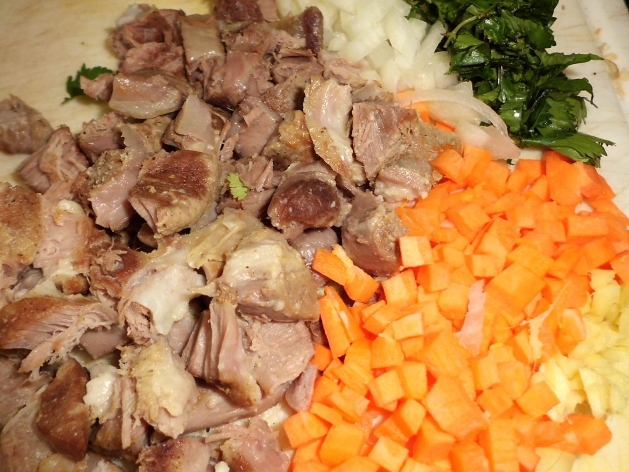 Lammfleisch aus der Brühe nehmen und von den Knochen lösen, Fett entfernen das Fleisch in kleine Würfel schneiden, so auch Möhren,Zwiebeln und Zucchini