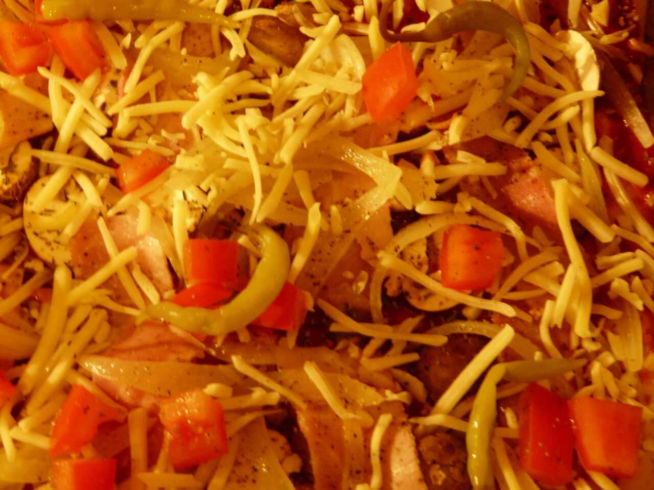 Tomatenwürfel und grüne eingelegte Chilis verteilen und bei 250° Grad 15 Minuten backen