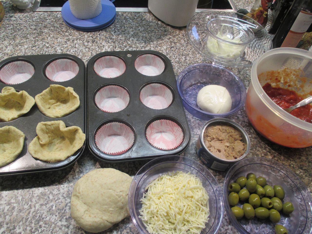Den Teig in Förmchen, Muffin-Backblech  verteilen